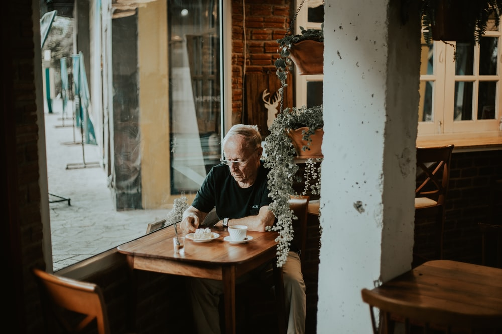 man in black shirt sits inside restaurant with coffee on front