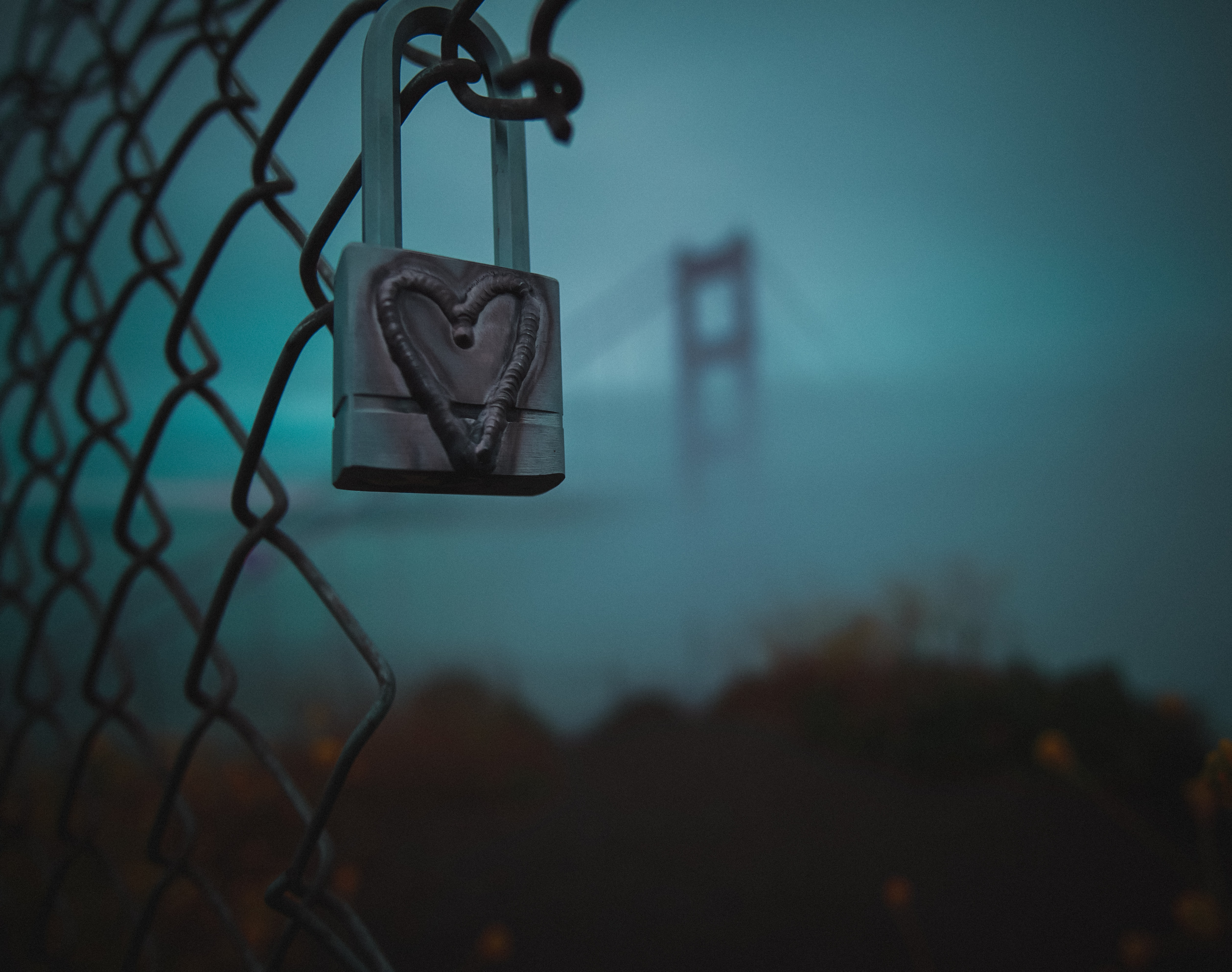 closeup photography of gray heart-printed padlock in gray metal fence