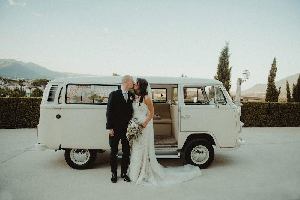 couple kissing beside white Volkswagen T2
