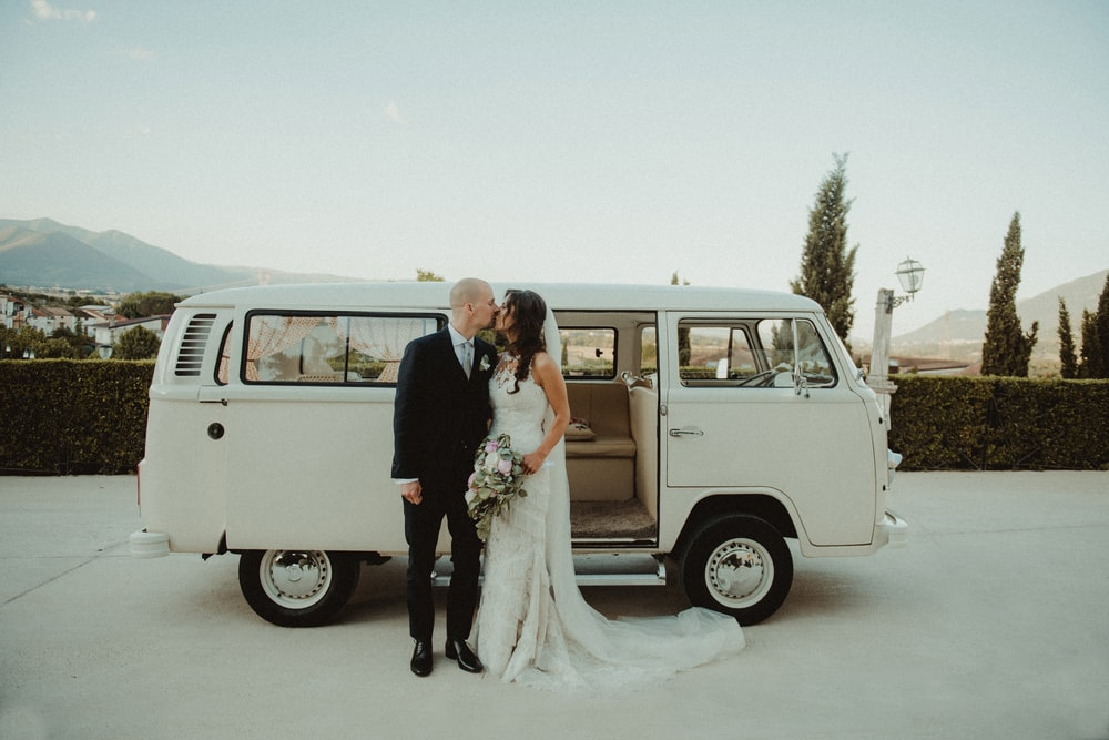 couple kissing beside white Volkswagen T2