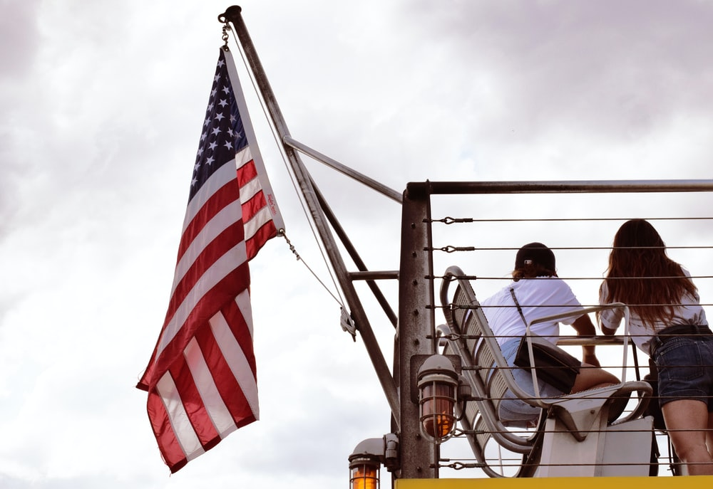 man in black jacket sitting on chair near us flag during daytime