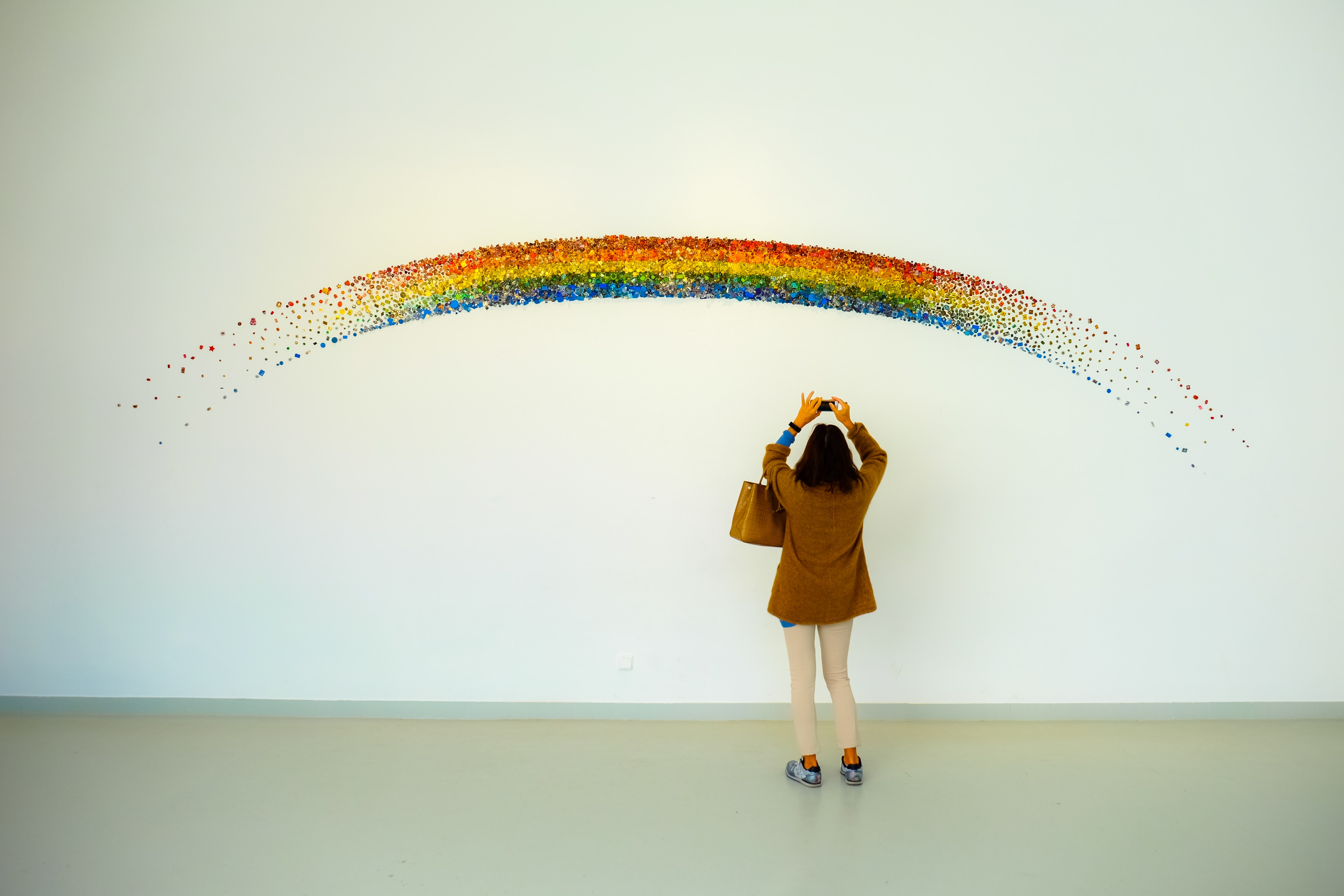 woman wearing brown jacket standing front of rainbow painting taking photo