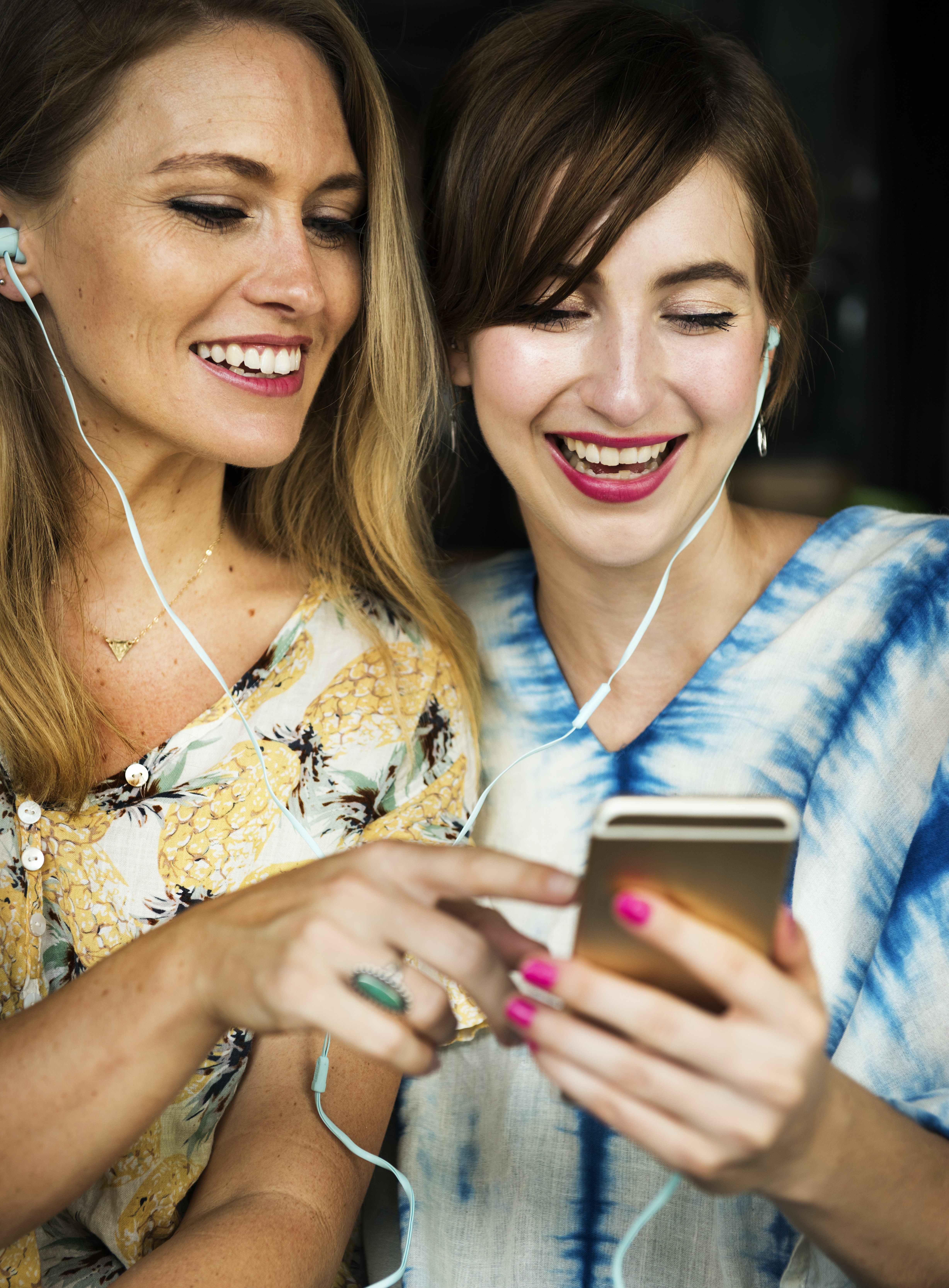 two woman listening on smartphone