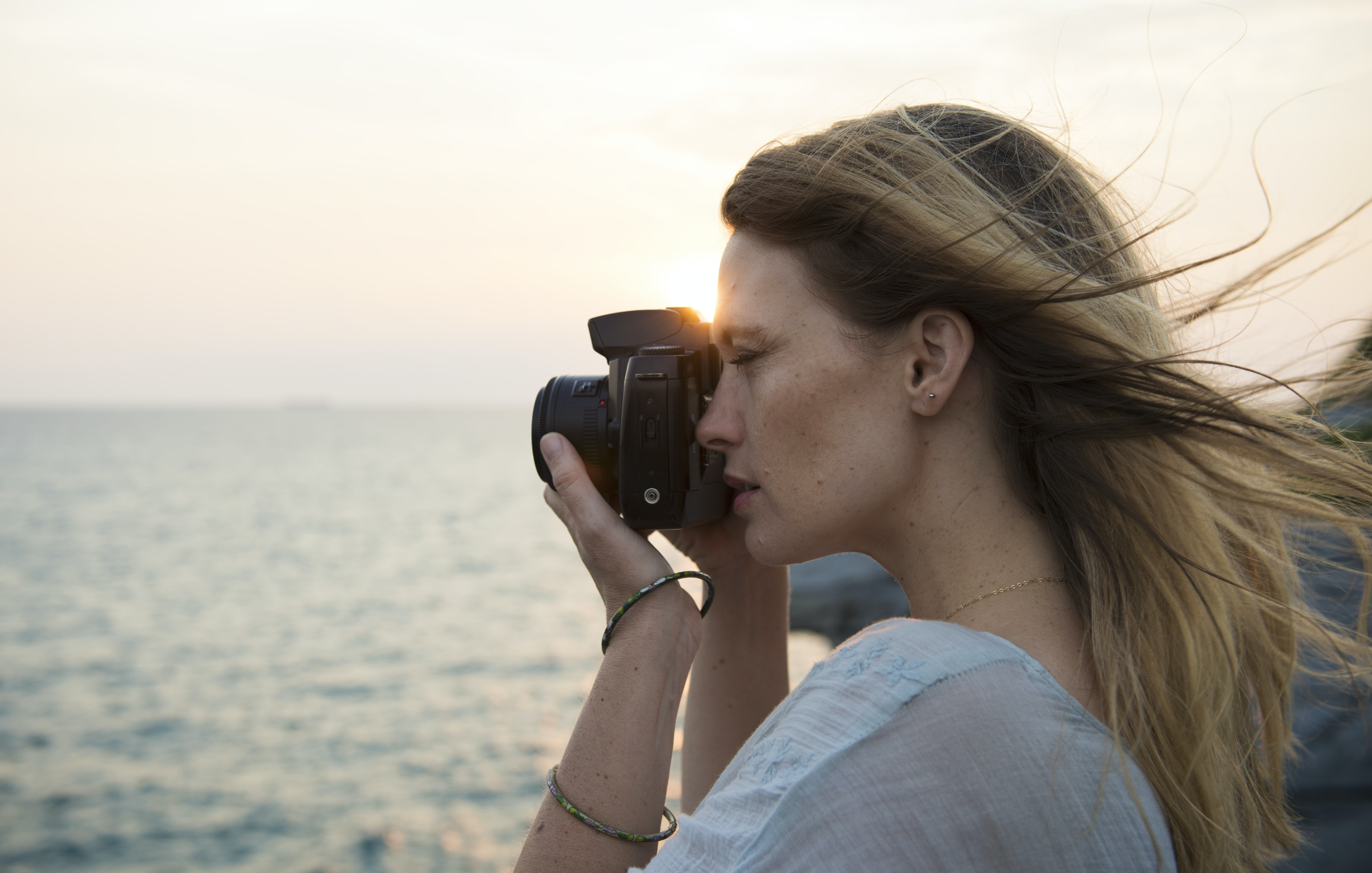 tilt-shift lens photography of woman holding SLR camera and taking photo while standing near body of water during daytime