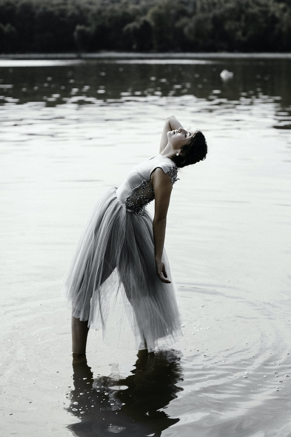 woman in gray dress standing on shallow body of water