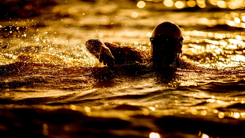 person swimming on body of water at nighttime