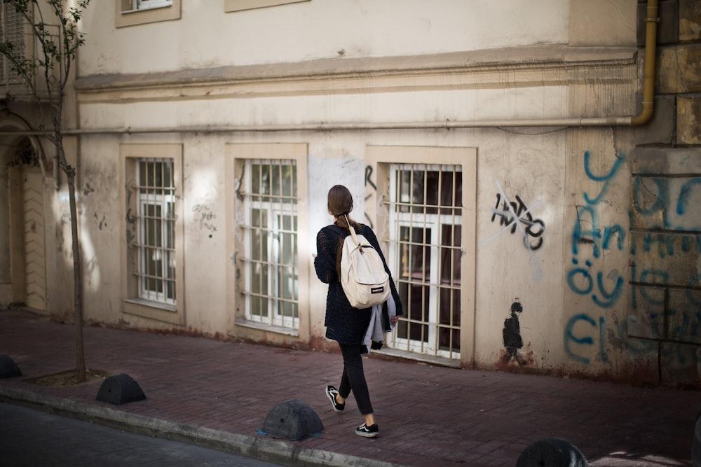 woman walking on sidewalk nearby beige structure