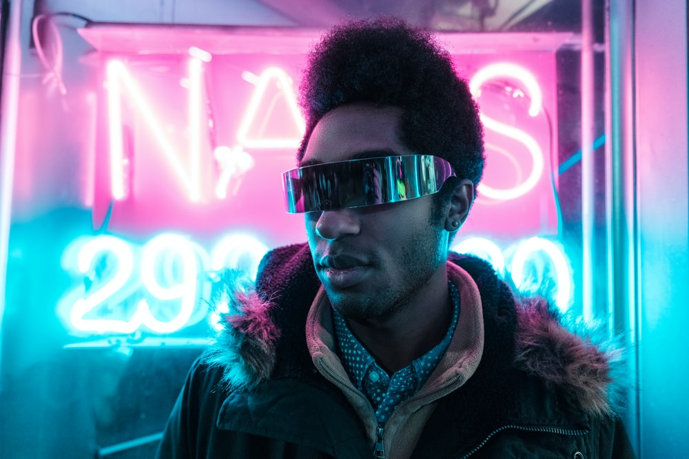 man wearing black parka jacket and black sunglasses in front of neon signage