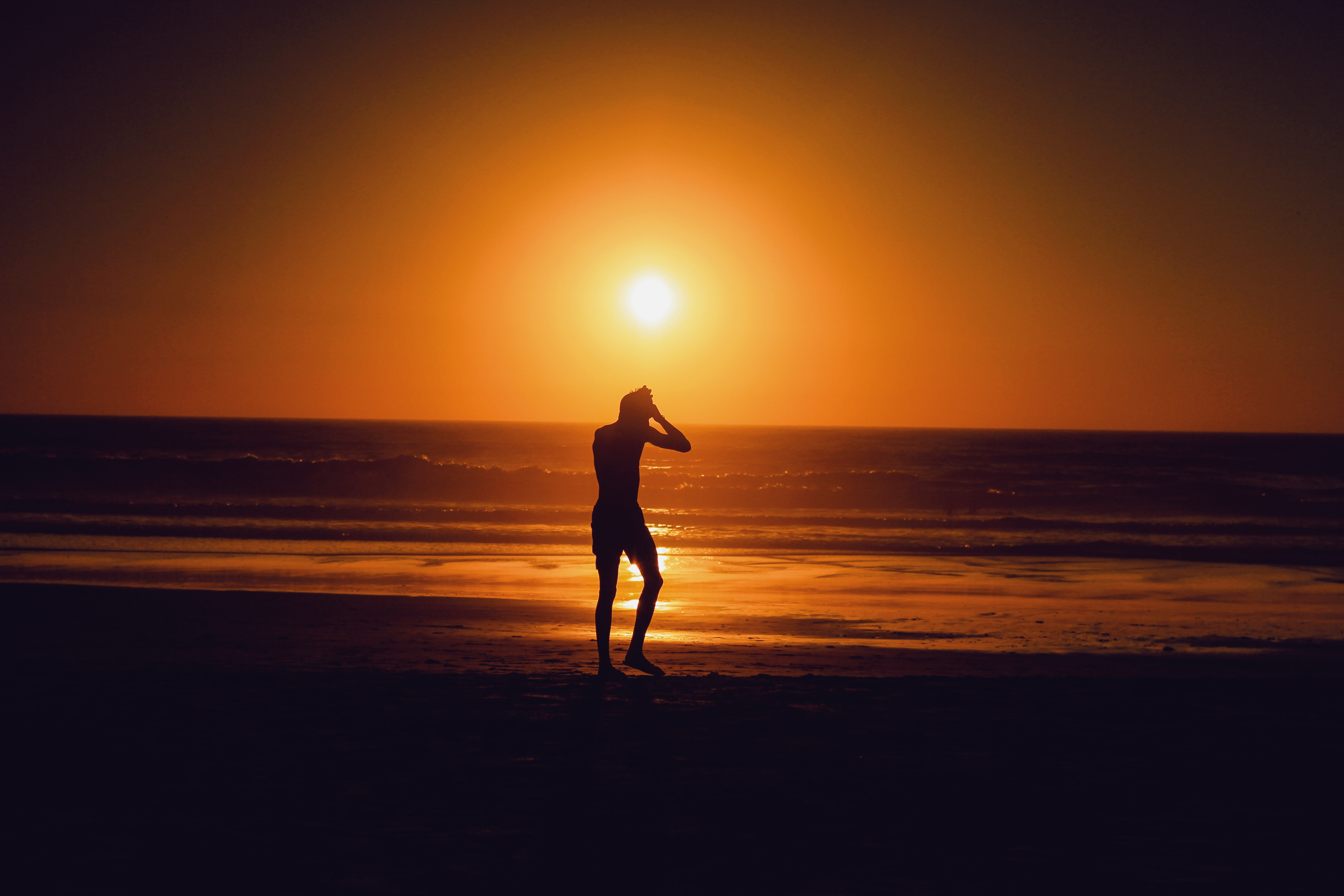 silhouette of person beside seashore during sunset