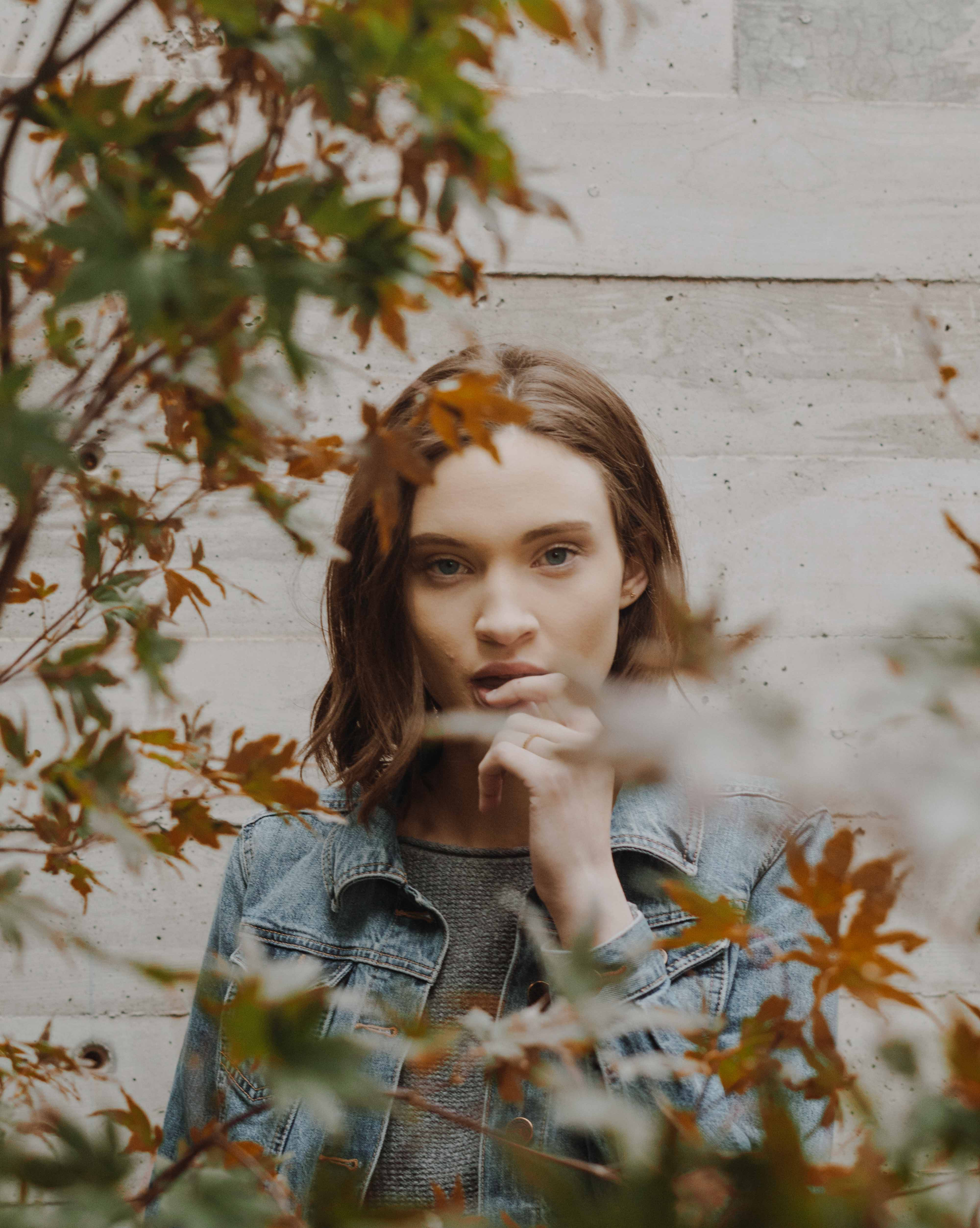 woman wearing blue denim button-up collared jacket holding lip behind brick wall in front of plants