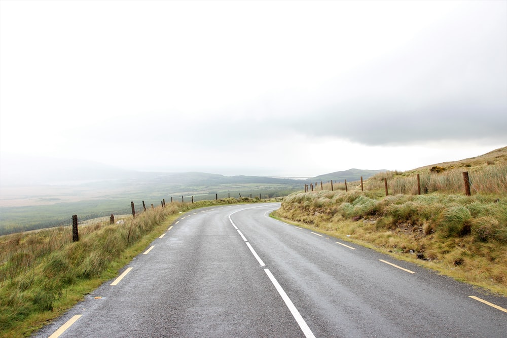 gray asphalt road near grass under gray sky during daytime