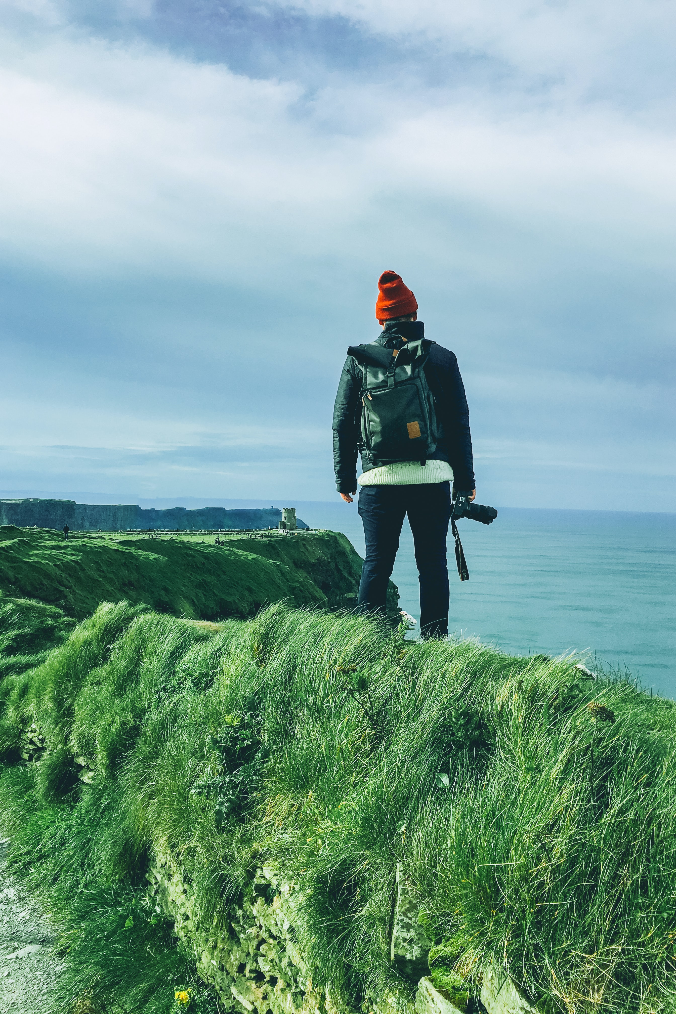 standing man holding DSLR camera on cliff looking to ocean under white sky