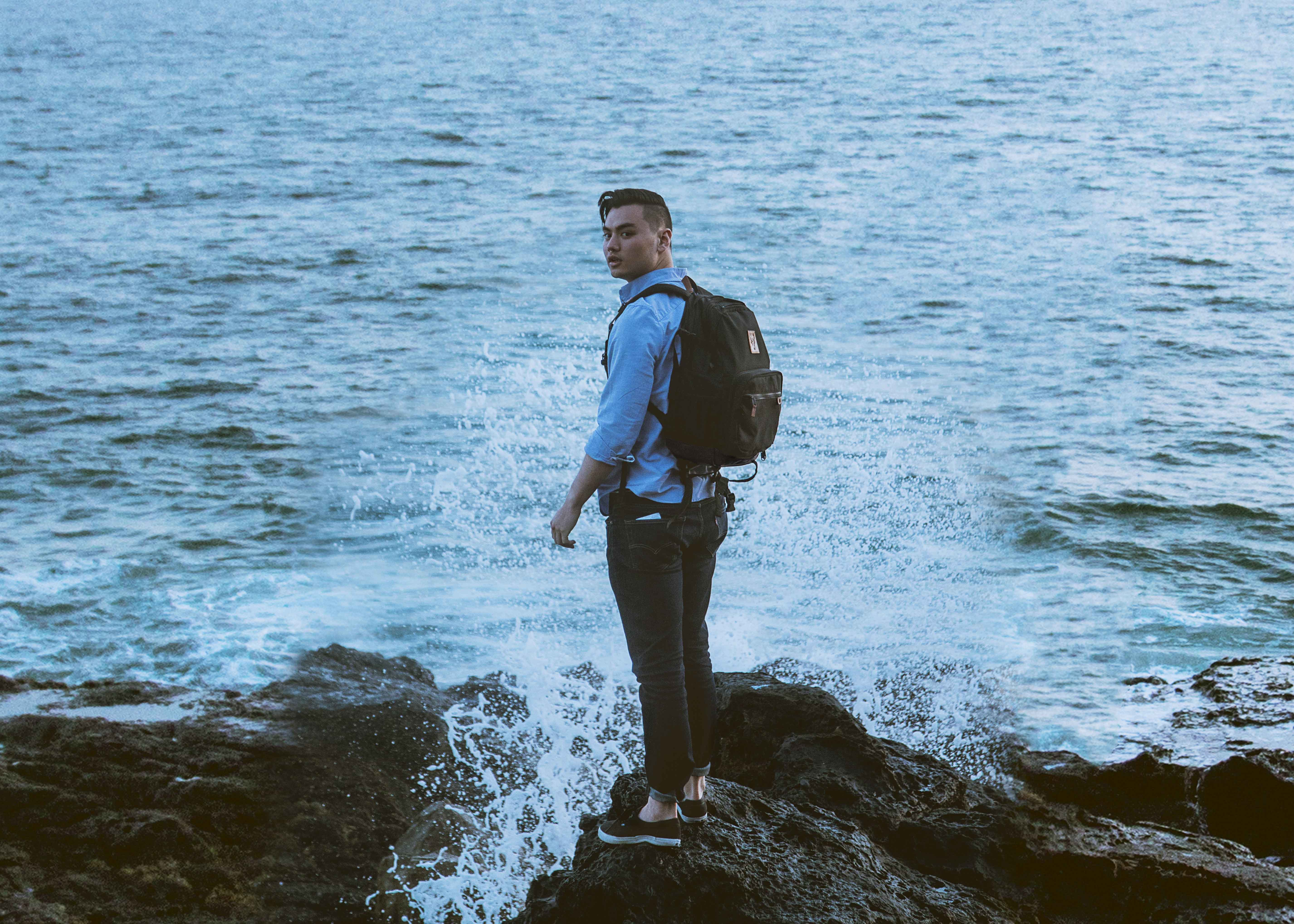 man standing on gray rock formation near body of water wearing backpack