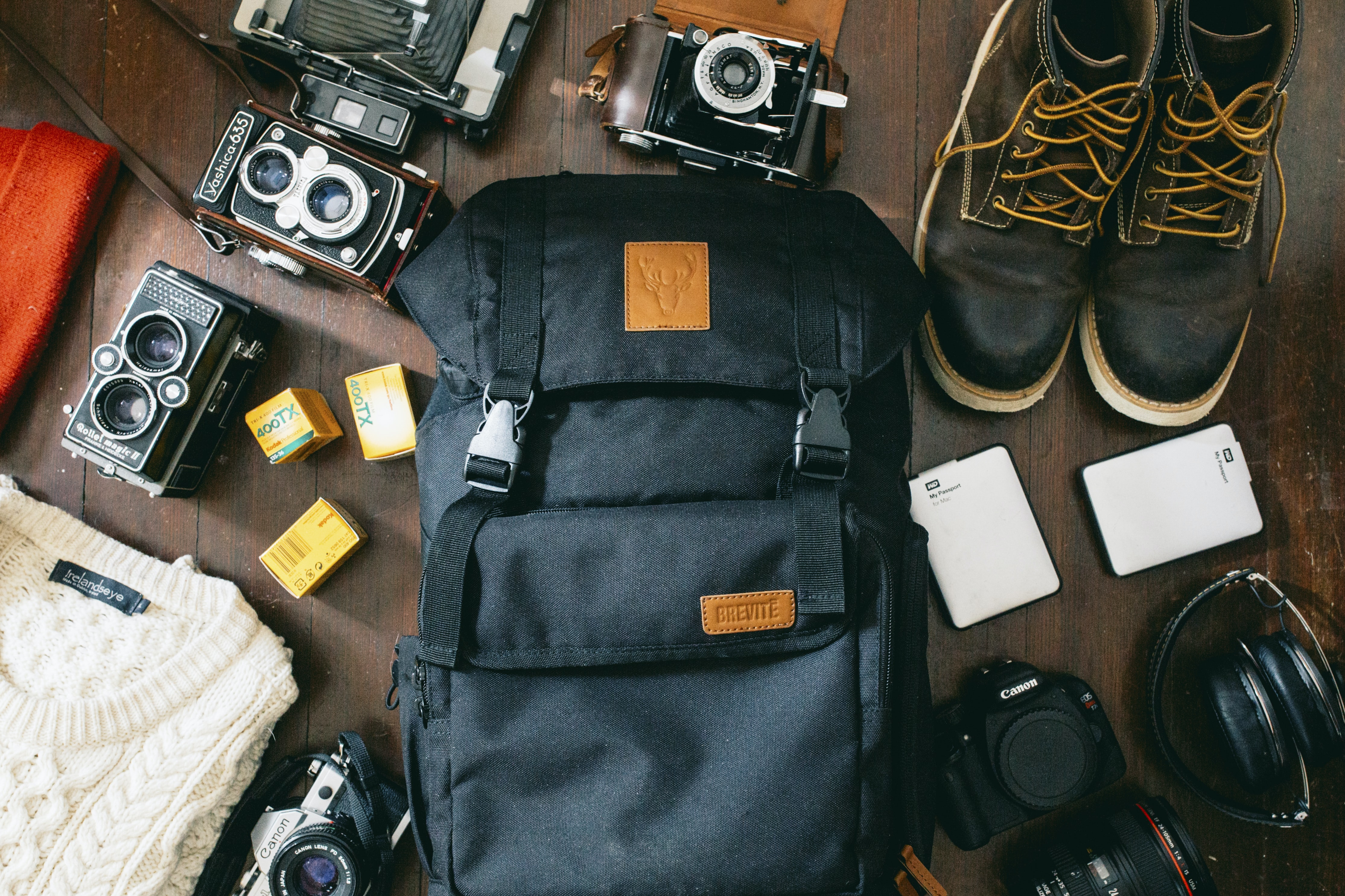 high-angle photo of black bag beside cameras, portable HDD and black leather lace-up boots