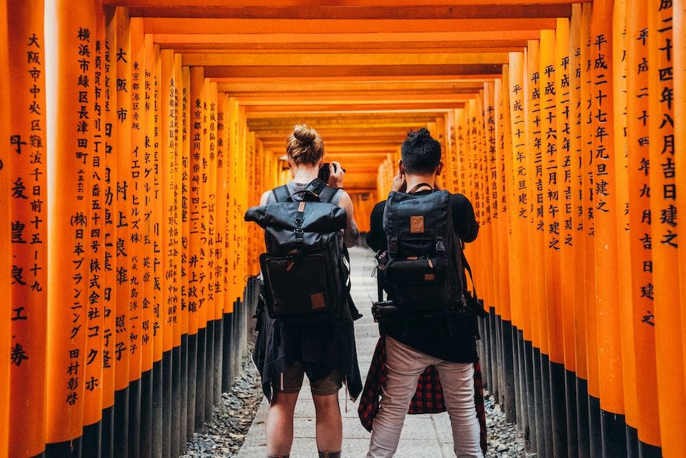 man and woman standing under orange kanji text print walls