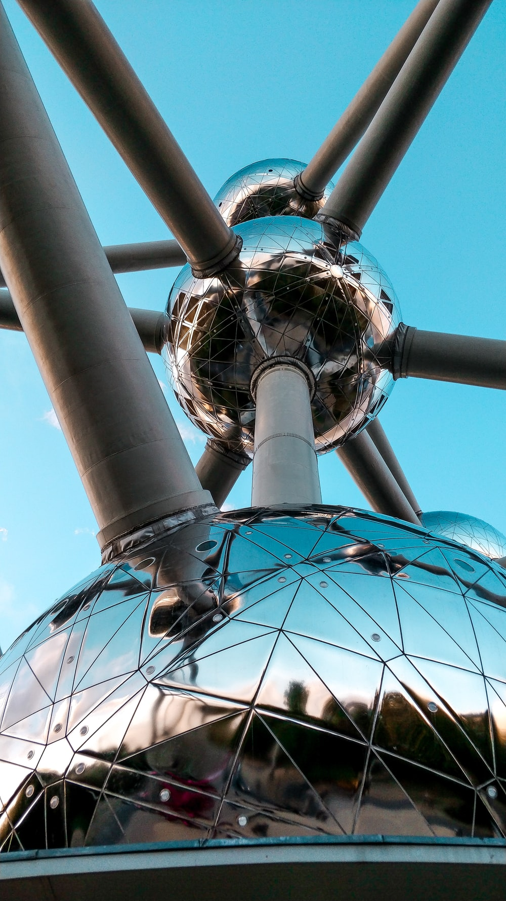 silver-colored spherical structure with attached gray pipes under blue sky