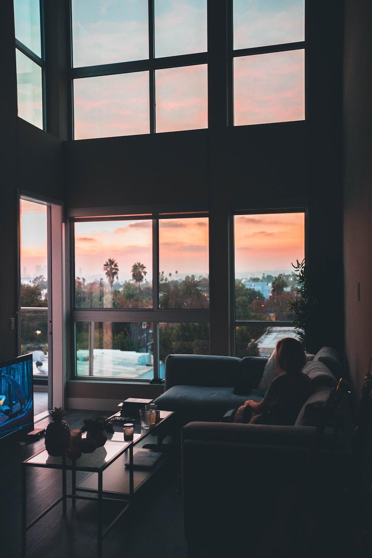 woman sitting on corner sofa beside coffee table near flat screen TV inside living room with glass window walls