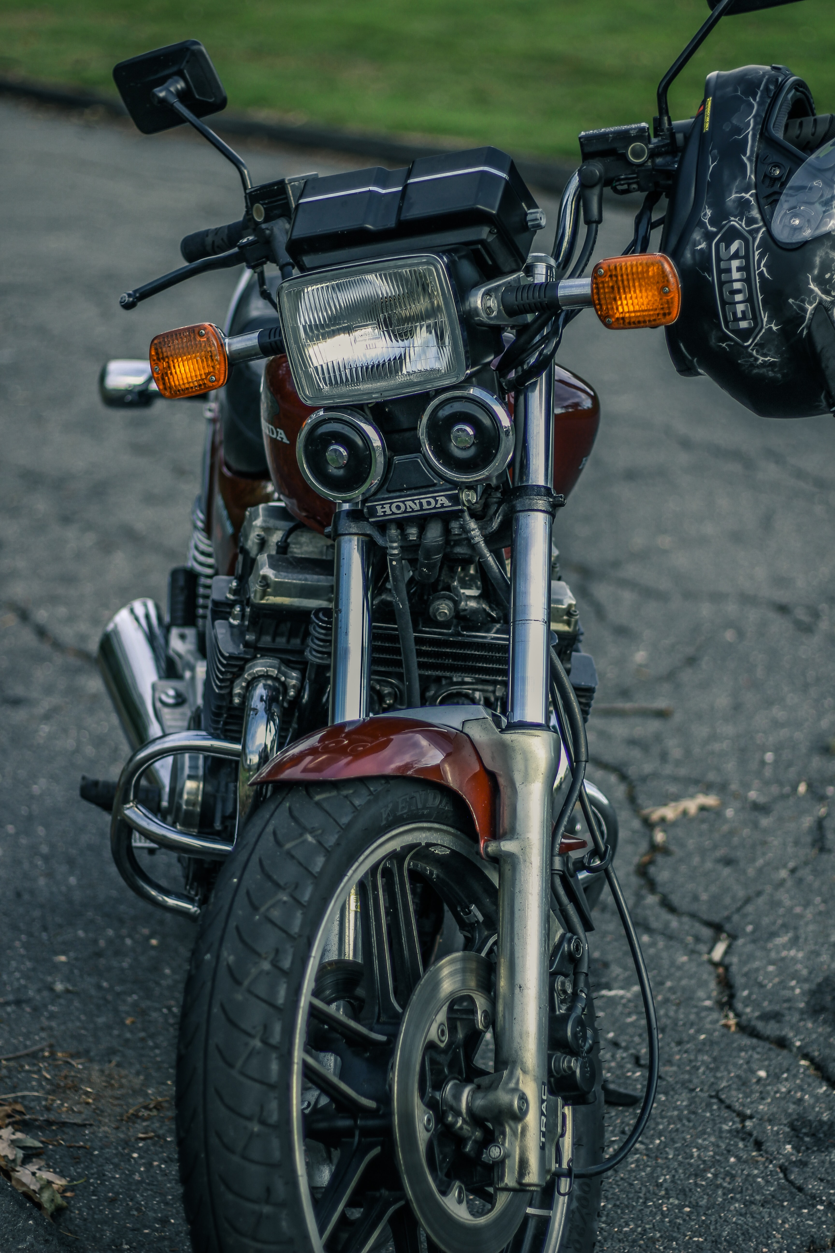 black and red Honda motorcycle on black concrete pavement