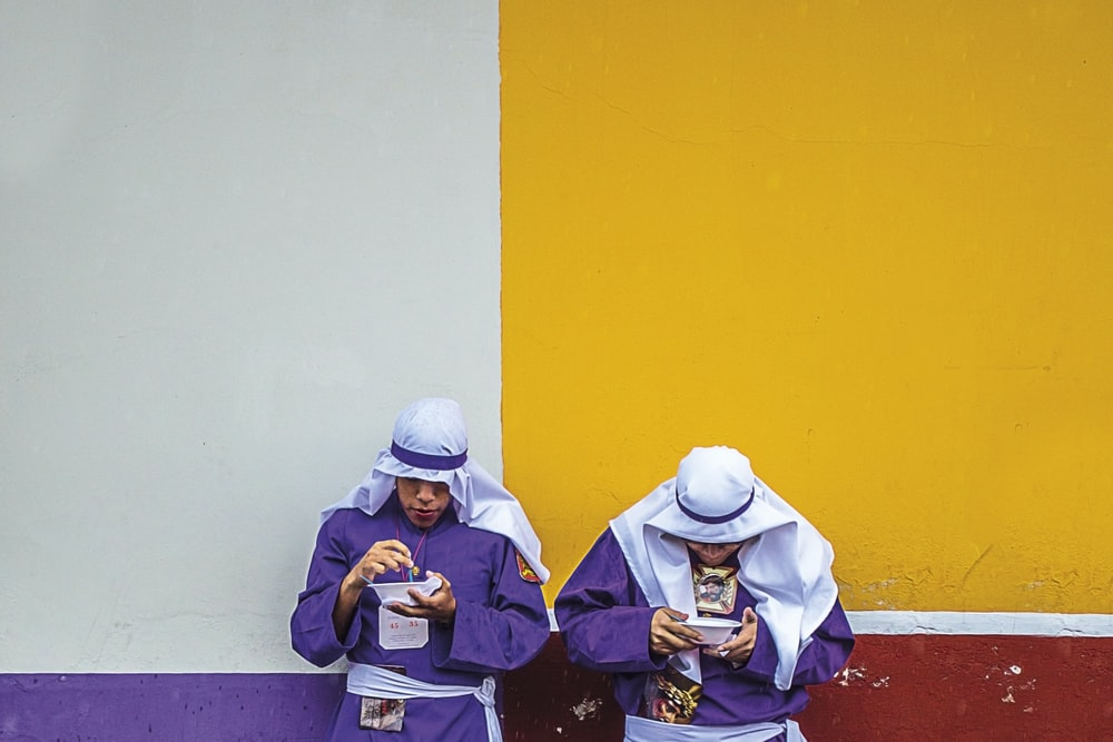 two standing men wearing purple long-sleeved top leaning on white, yellow, purple, and red painted wall