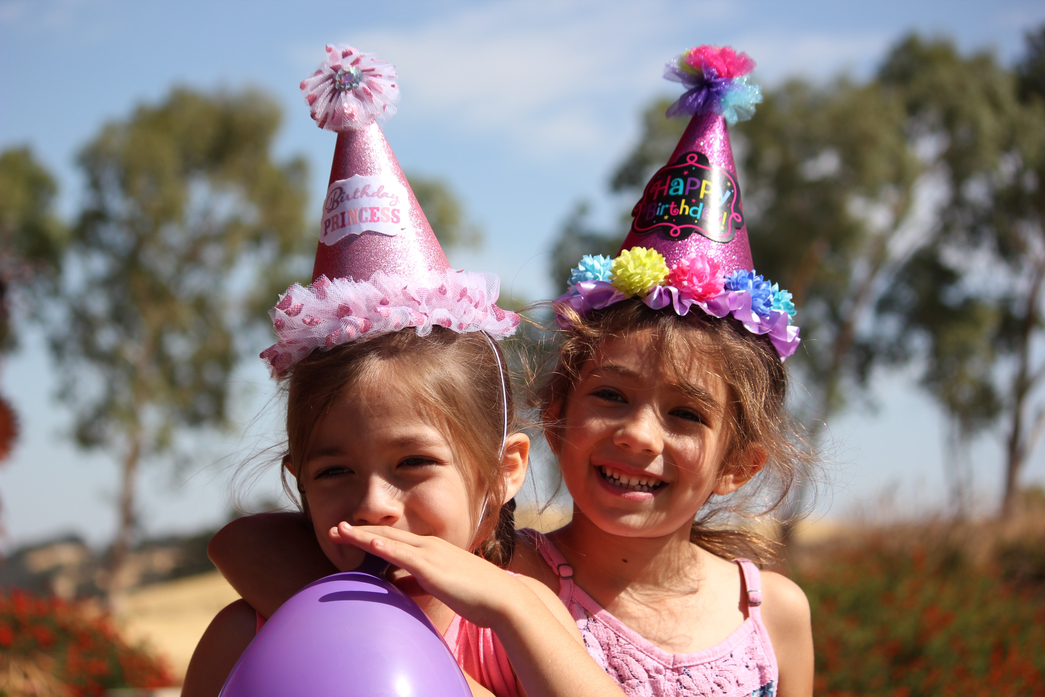 girl in left blowing purple balloon beside girl wearing pink birthday hat
