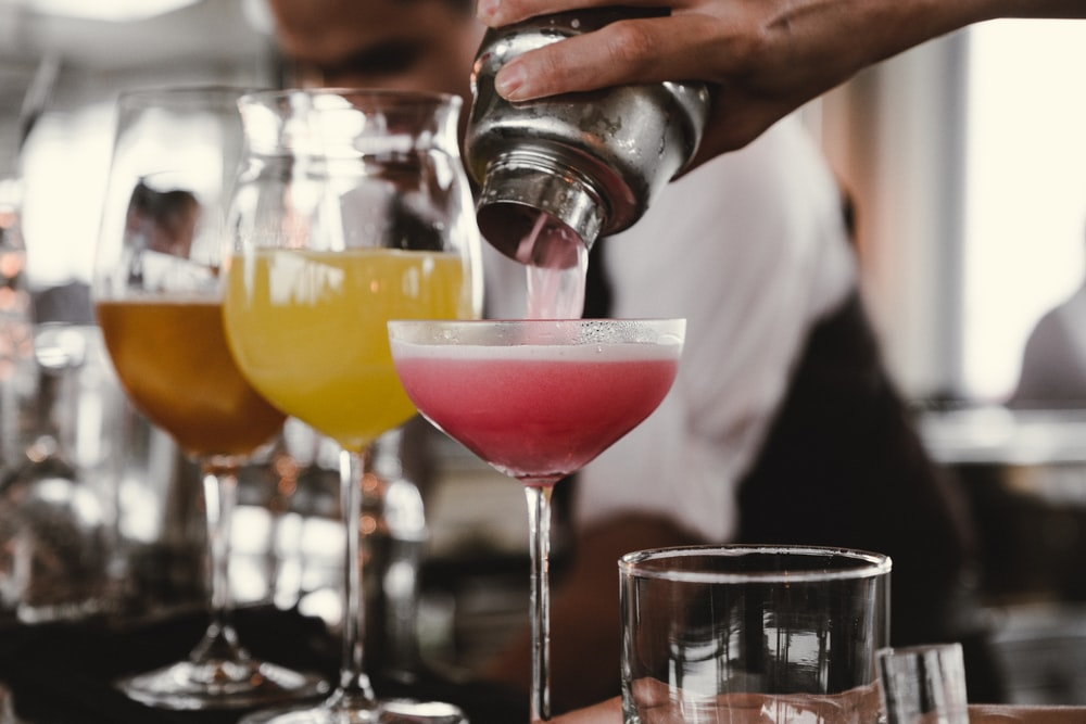 person holding cocktail shaker pouring liquid in glass during daytime