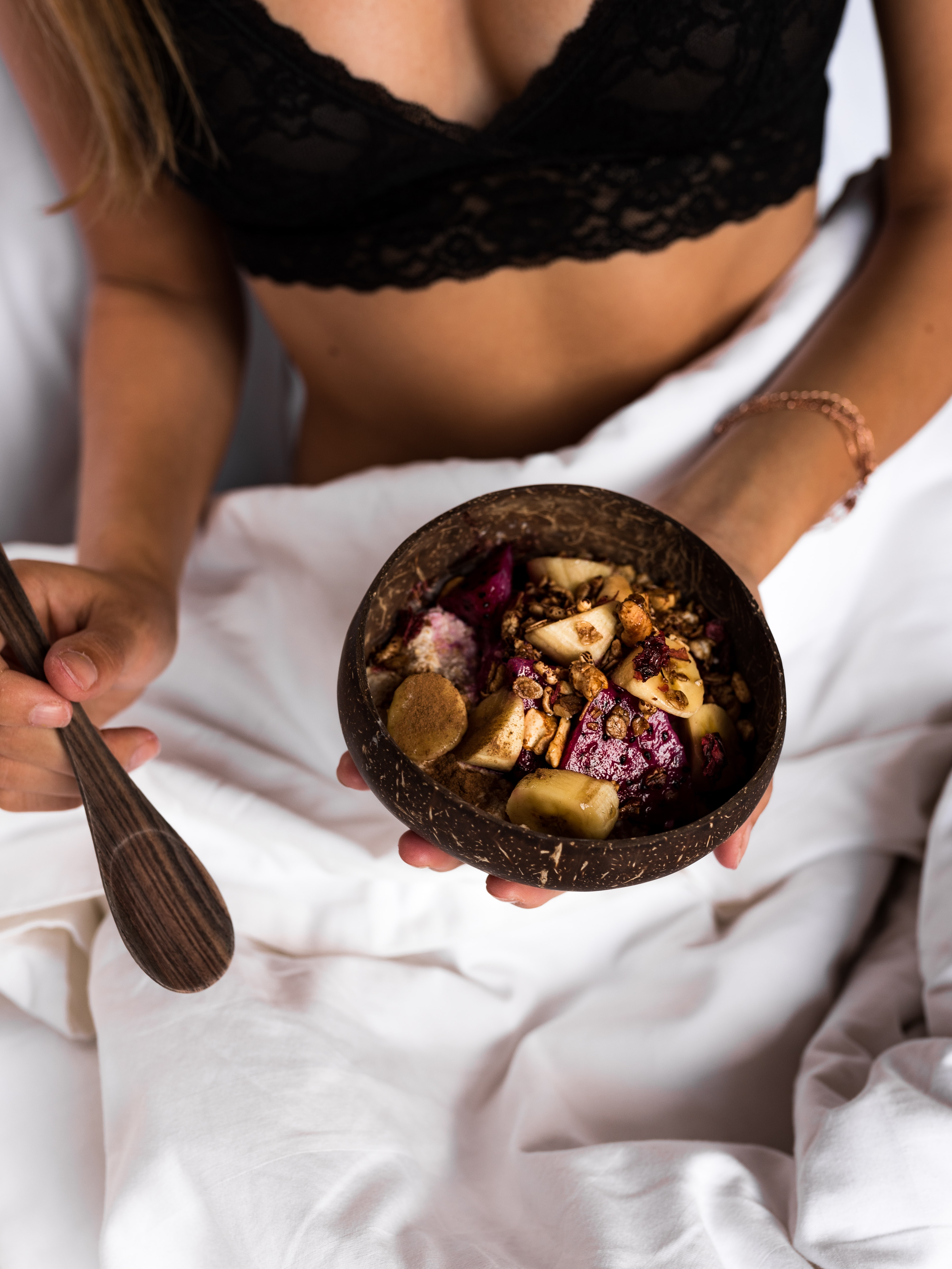sliced fruits on coconut shell bowl on woman's hand in bed
