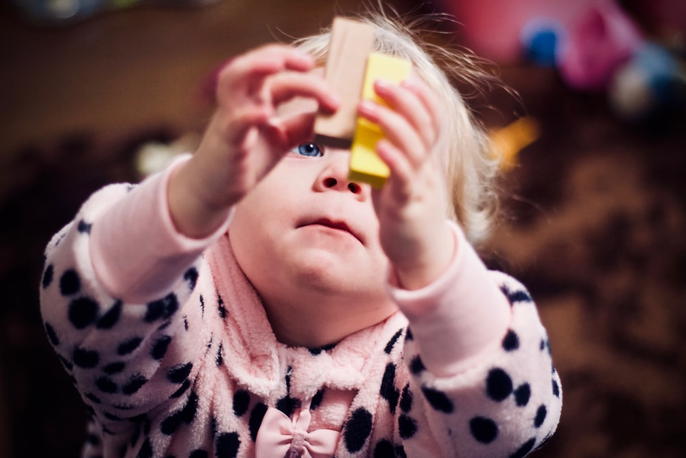 toddler playing with two wooden blocks