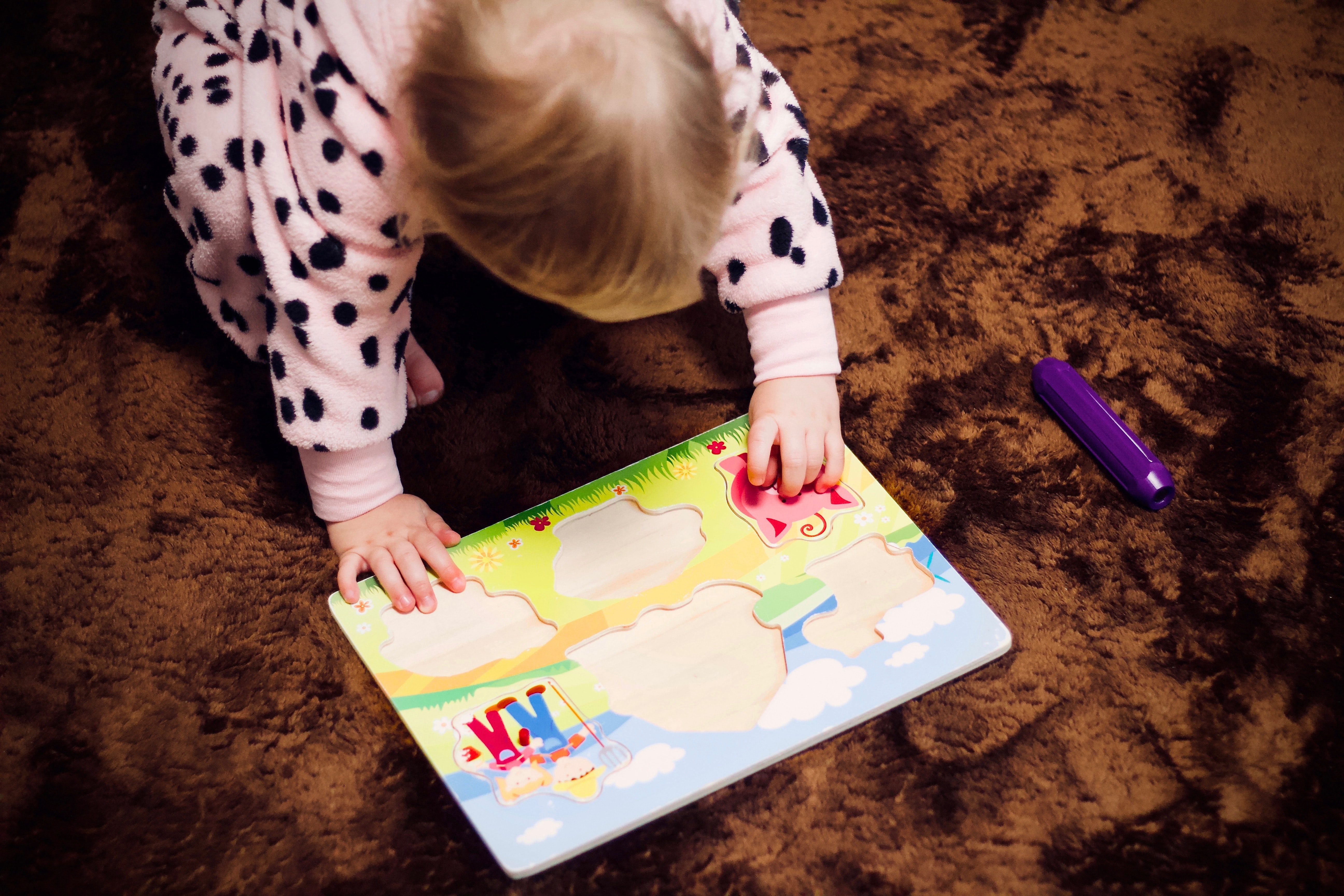 toddler's solving puzzle on floor