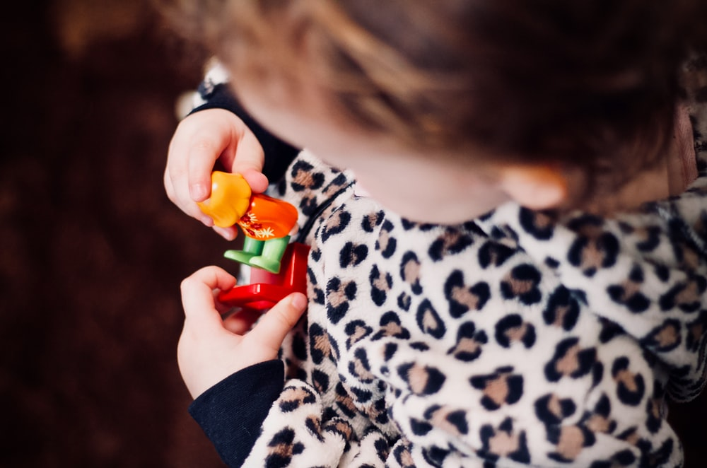 girl holding plastic toys in macro photography