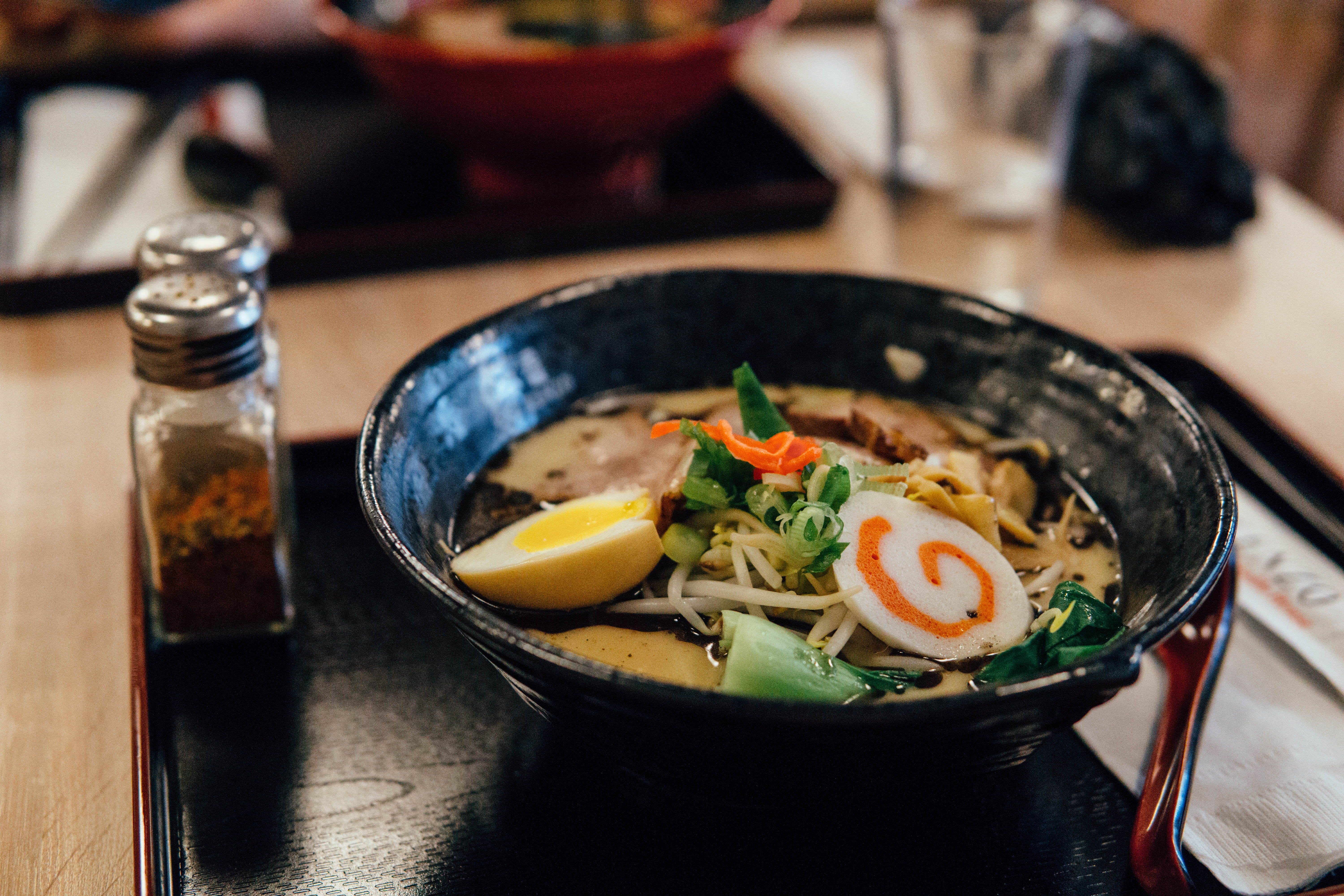 focus photography of ramen in bowl with condiment shakers