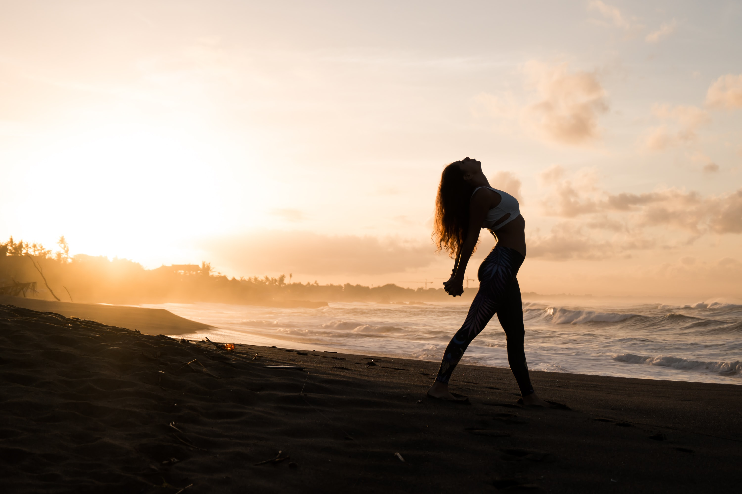 silhouette of woman stretching her arms on seashore during sunrise
