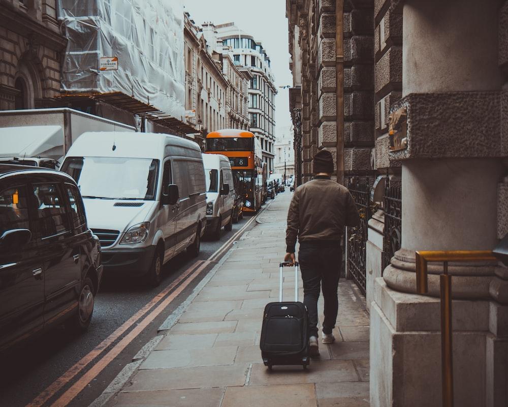 man holding luggage walking near road during daytime