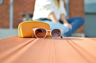 sunglasses beside a purse product teams background