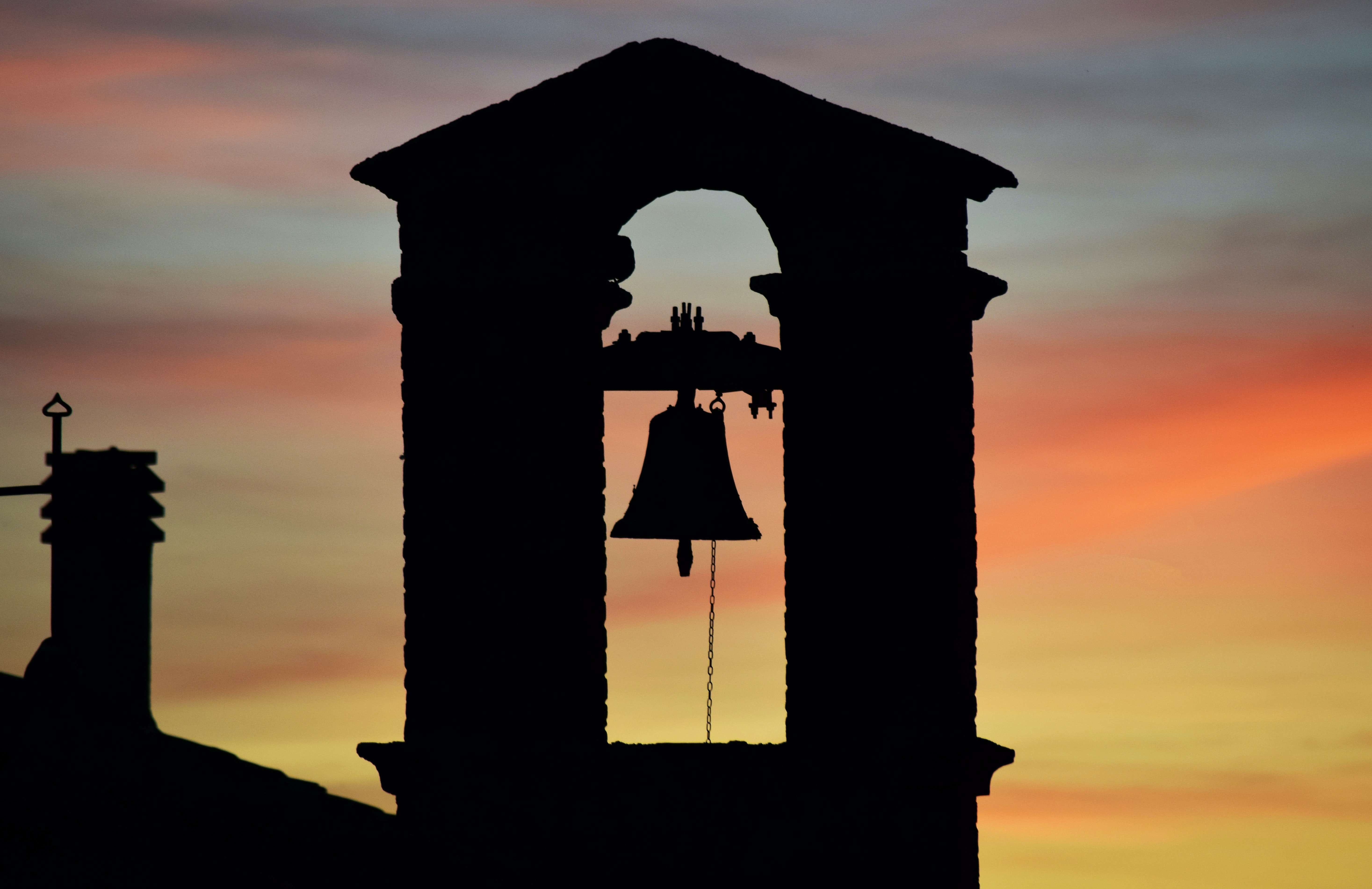 silhouette of church bell during sunset