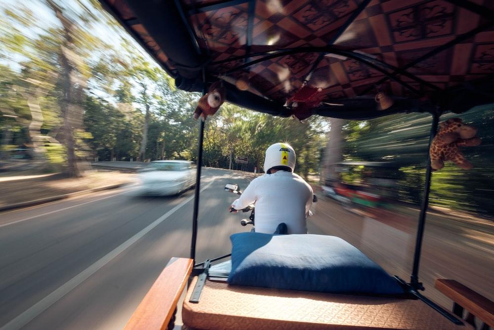man riding auto rickshaw during daytime