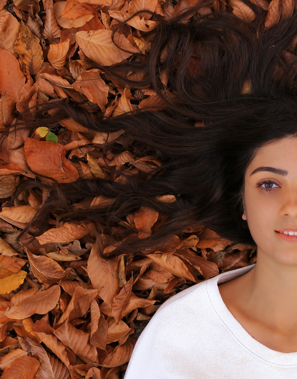 woman lying on ground with brown leaves