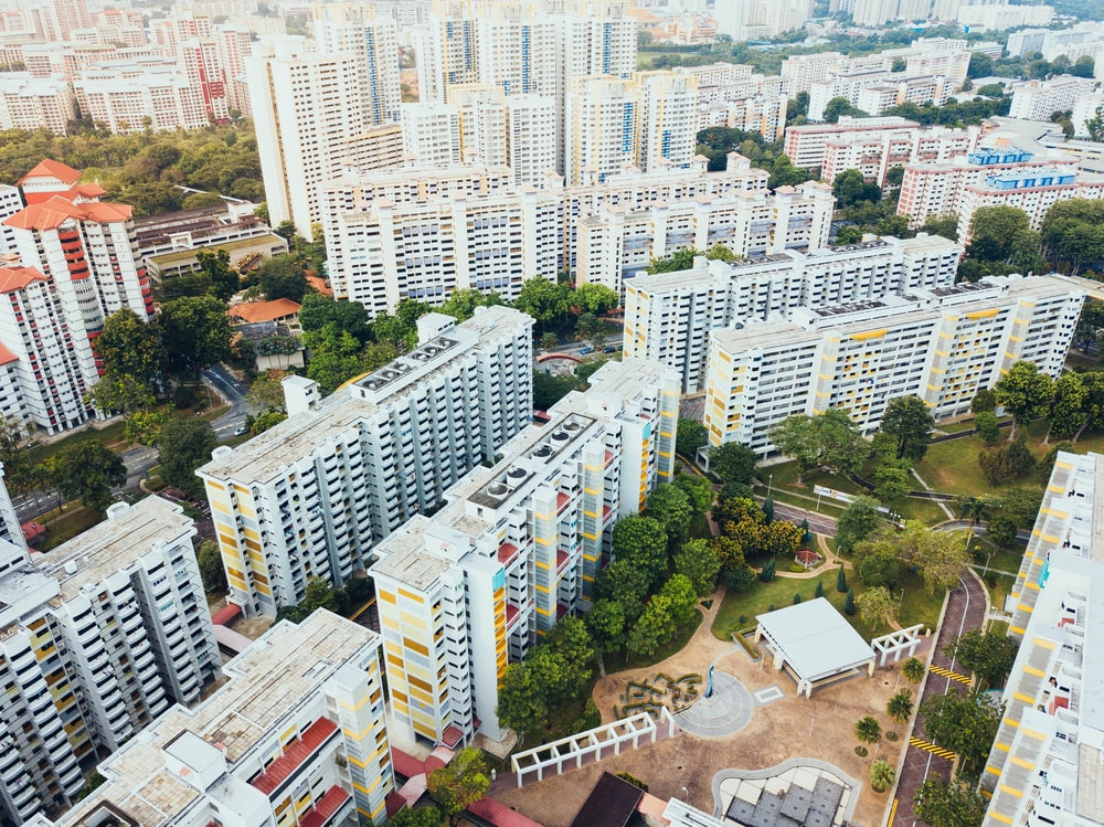 aerial photo of white concrete buildings near green leaf trees