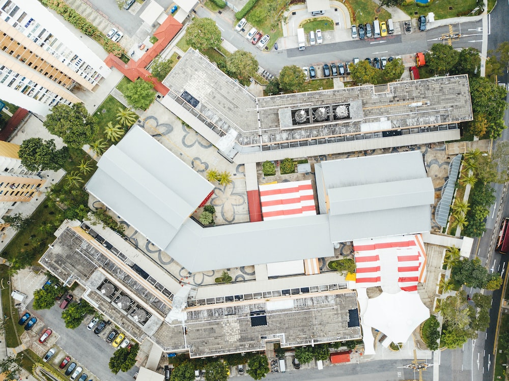 top view photography of buildings beside road and trees at daytime