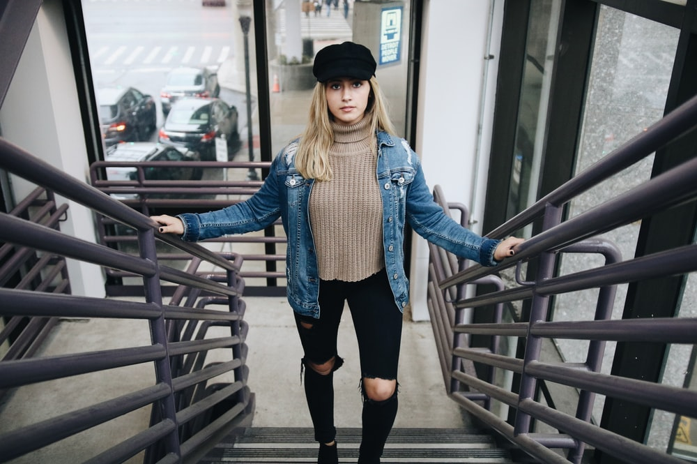 woman wearing blue denim jacket, brown sweater, black jeans, and hat standing in stair
