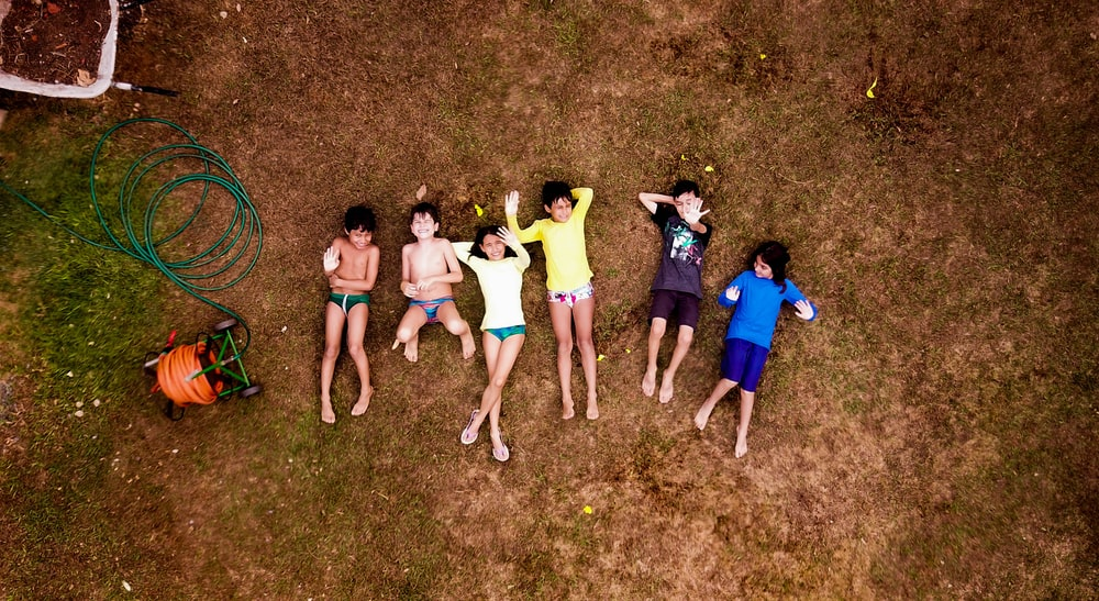 group of kids beside garden hose reel