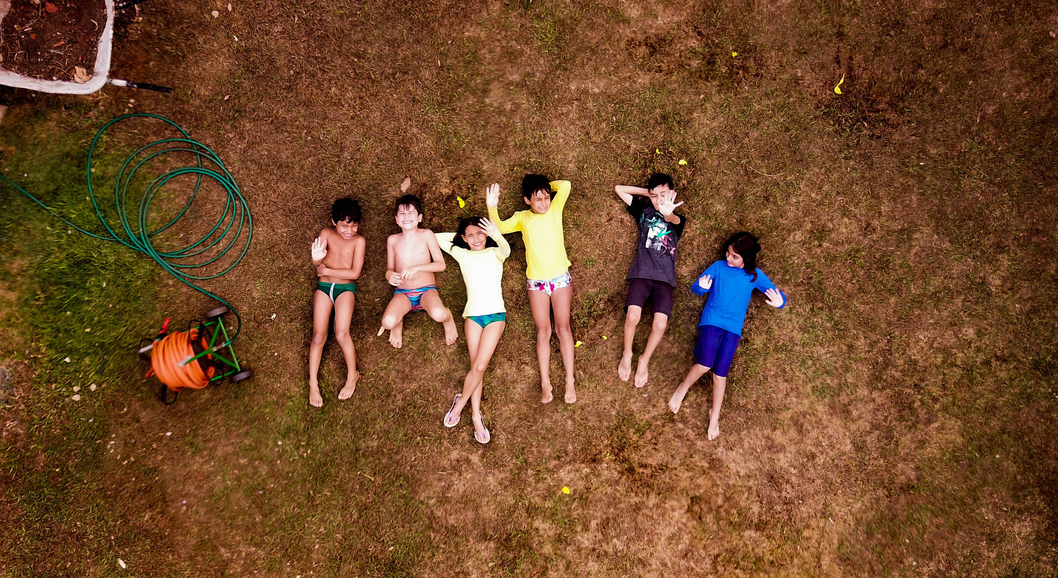 group of kids beside garden hose reel