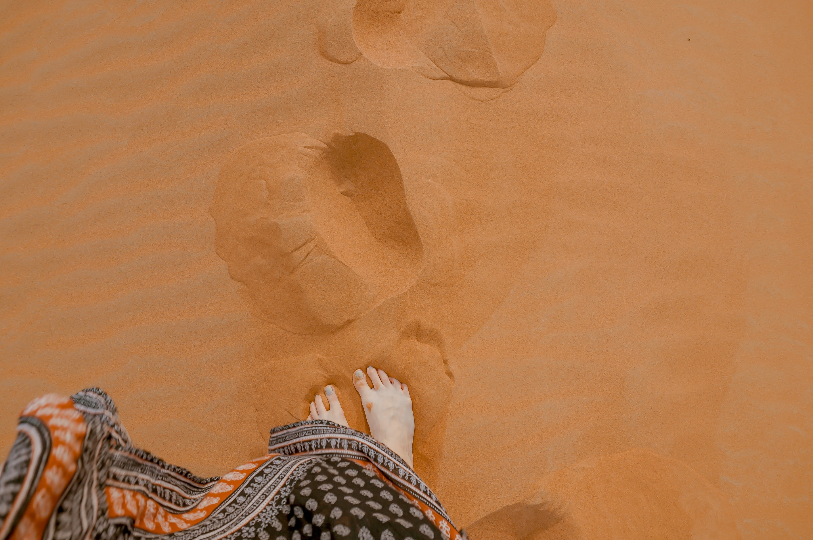 photo of person standing on orange sand