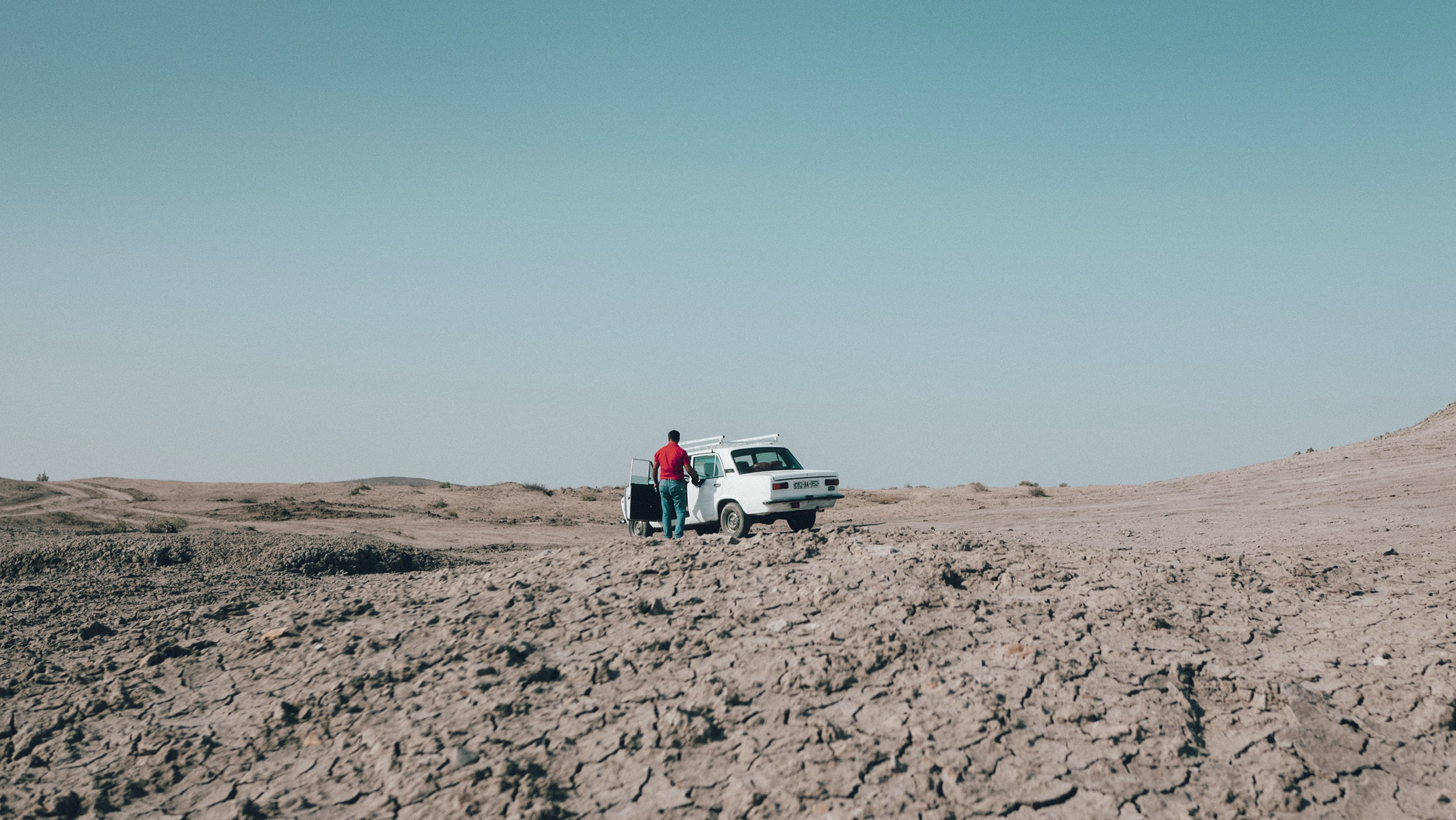 person standing beside vehicle on desert at daytime