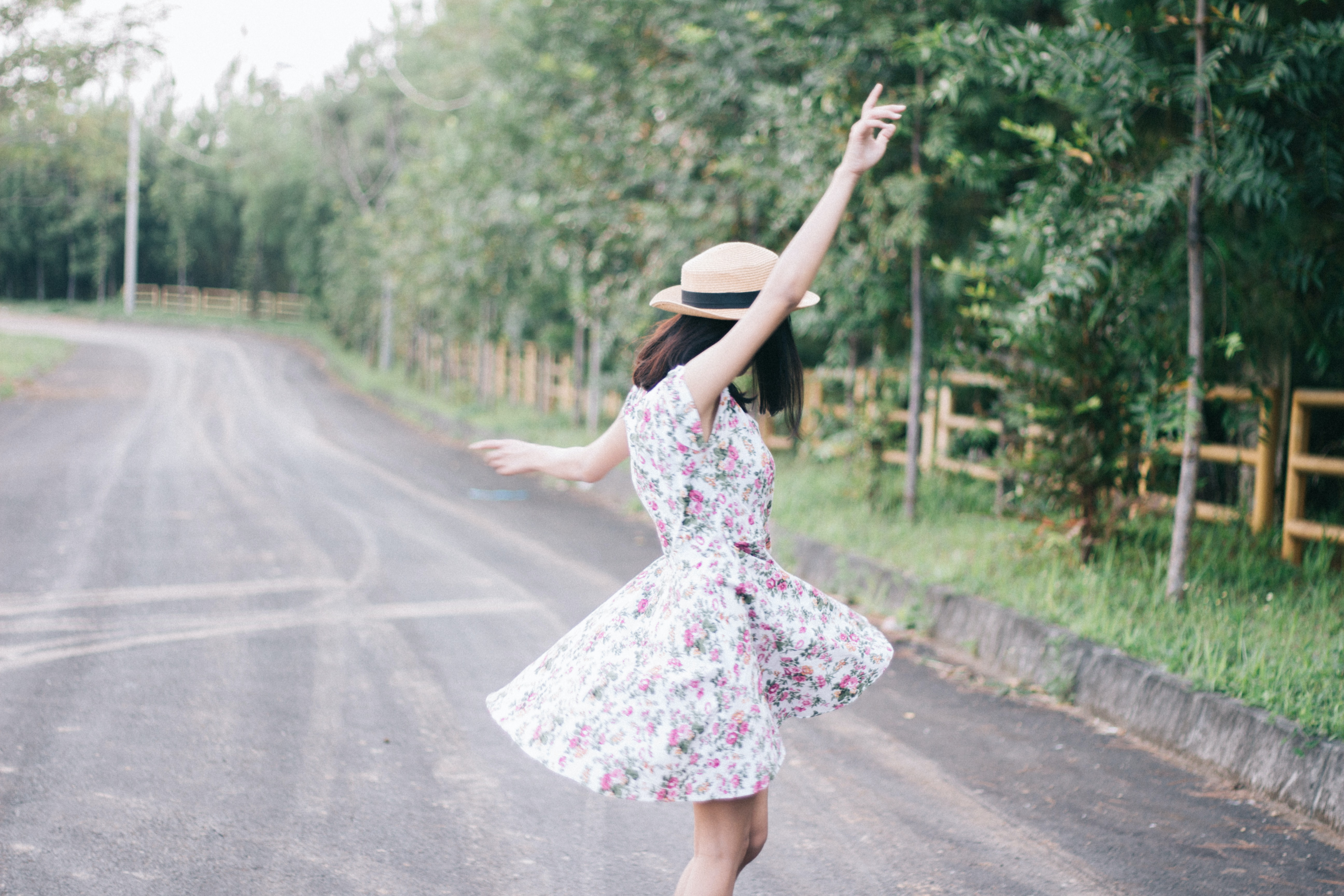 woman wearing white floral dress standing on concrete road