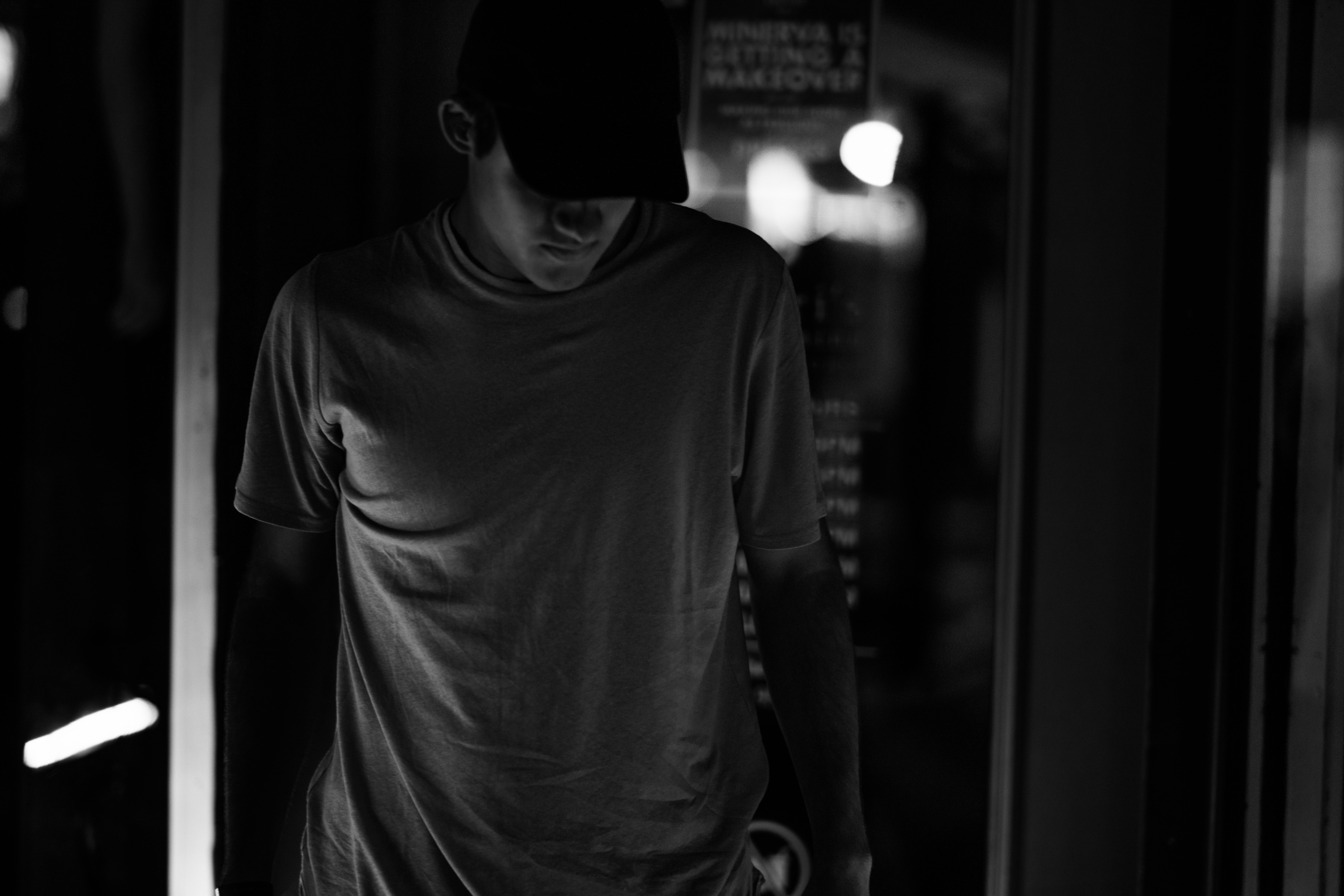gray scale photography of man wearing crew-neck shirt and trucker hat