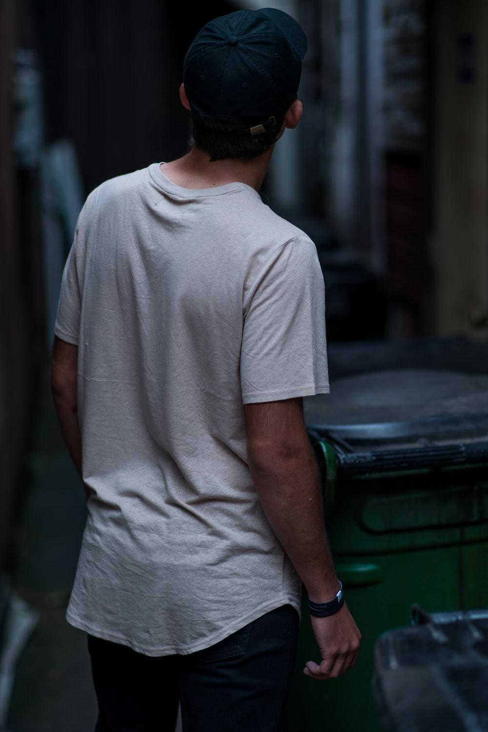 man wearing white shirt beside wheelie bin