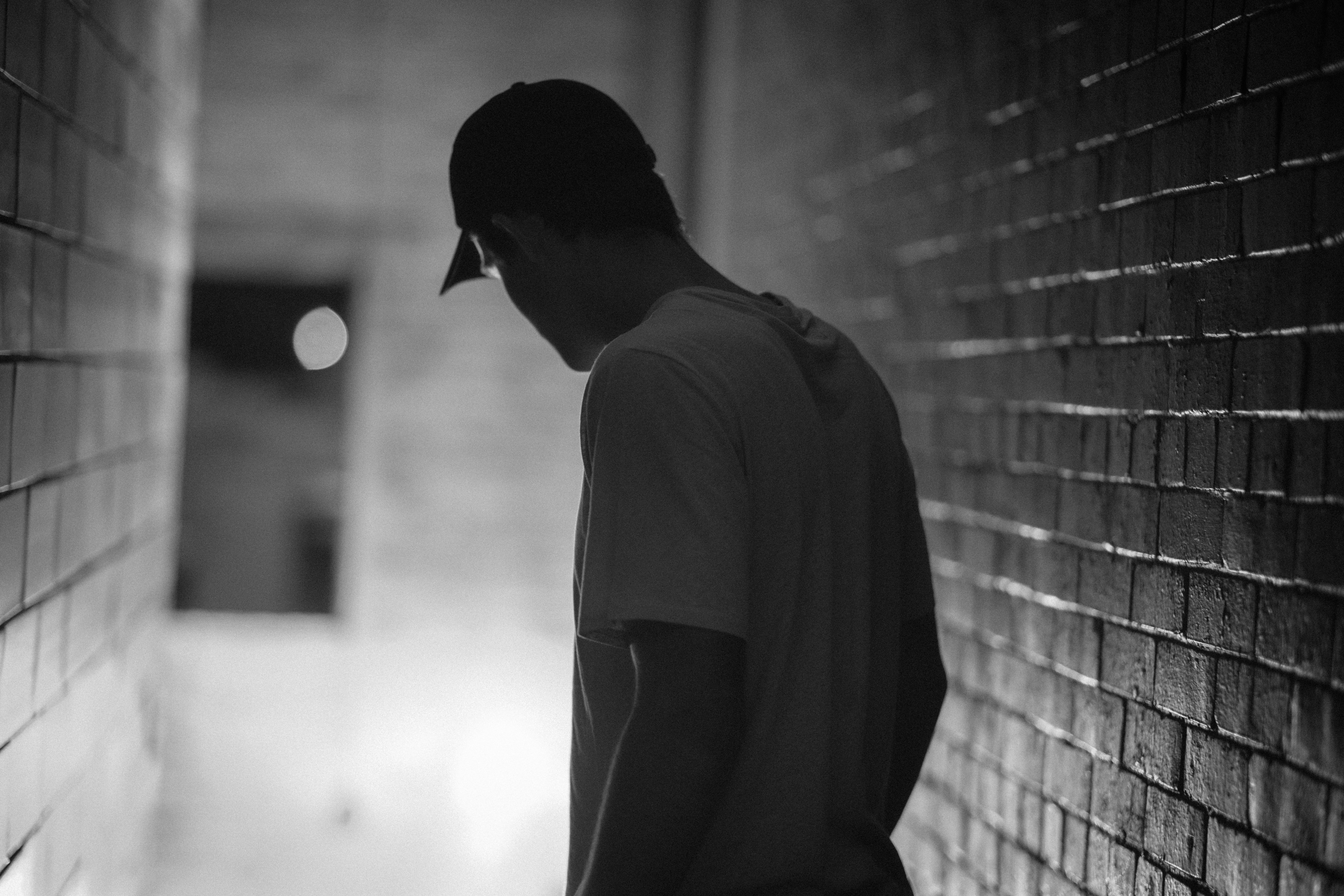 photography of man looking down surrounded by brick walls