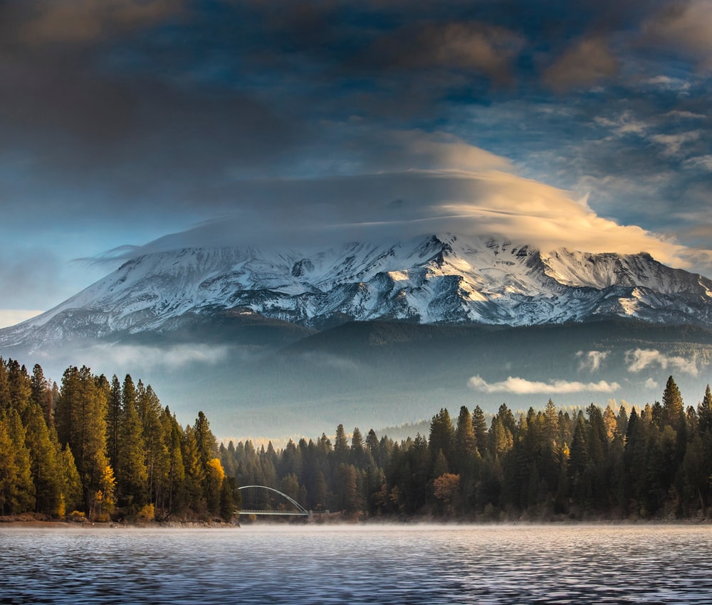 landscape photography of trees and body of water near snow covered mountain at daytime