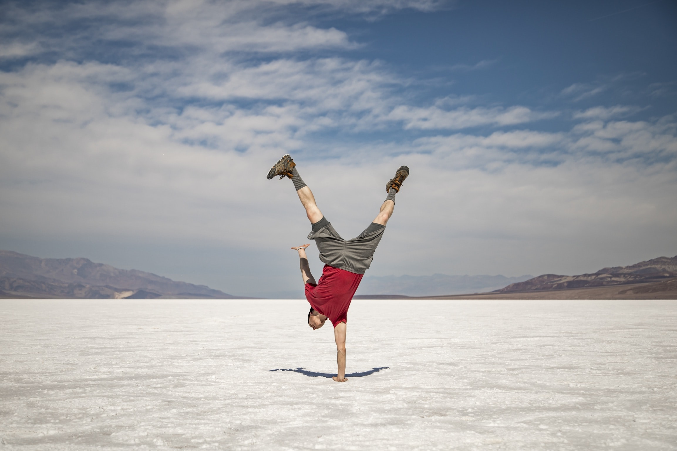 man doing one hand stand under white skies at daytime