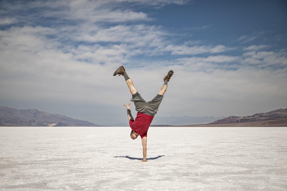 man doing one hand stand under white skies at daytime